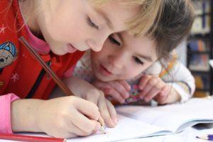 deux enfants en train d'écrire et dessiner, illustre le concours Librius 2022